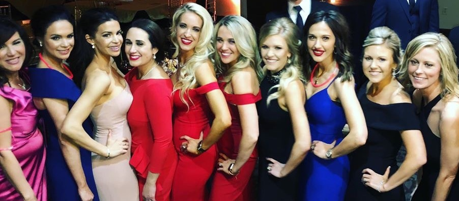 Ladies in fancy dresses standing in a line